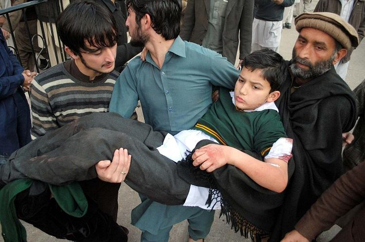 Civilians+carry+a+wounded+child+out+of+the+school+attacked+by+militants+in+Peshawar.