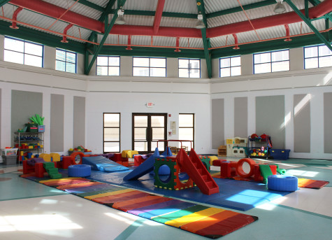 In the gym, the kids are able to utilize many different toys and have a large, open space to run around and play.
