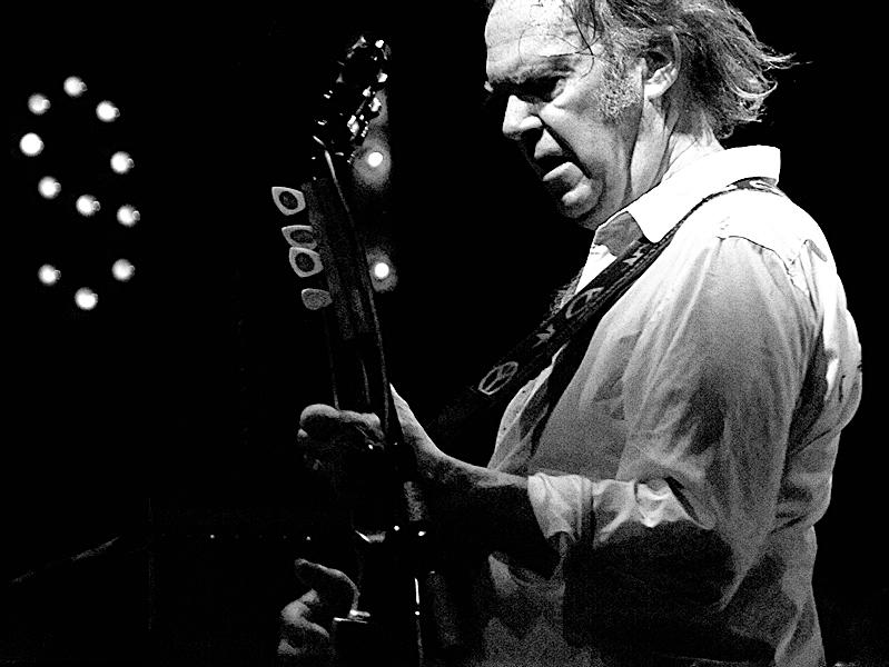 Neil Young rocks out with his guitar on stage.