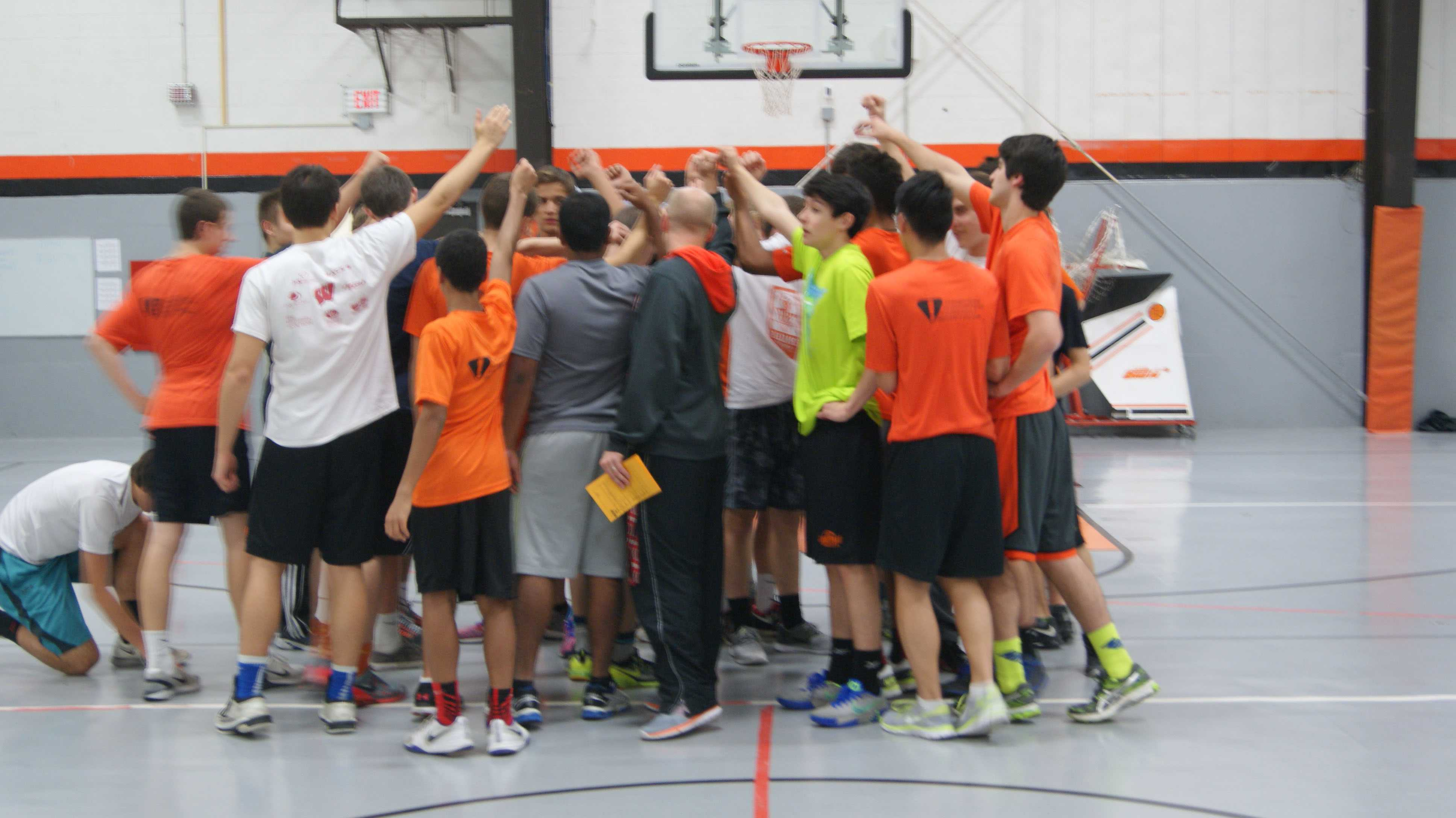 A group of players gather with the coaches and discuss what they can expect from this practice.