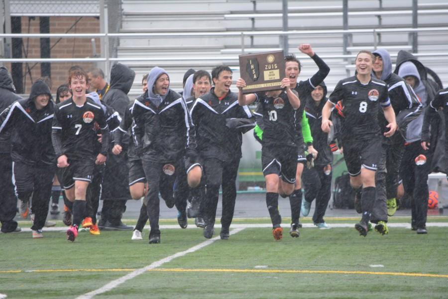The team celebrates its sectional title Saturday in the pouring rain.