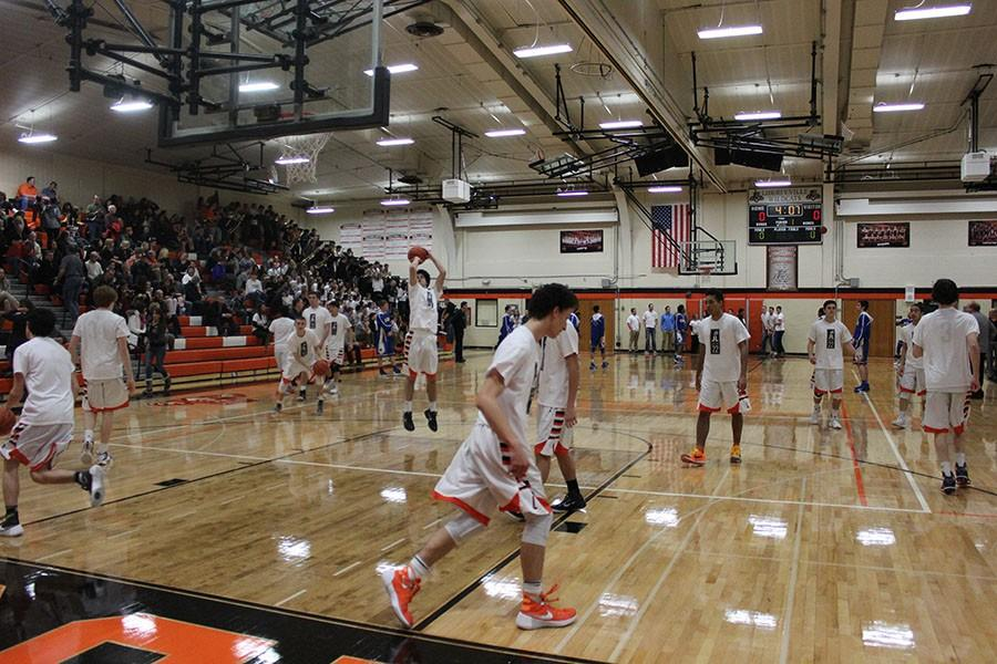The varsity boys basketball team warms up on the court before facing conference opponent Warren on January 5.