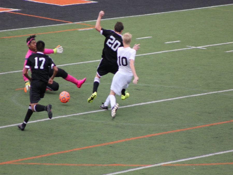Senior+Ryan+Bogan+kicks+the+ball+past+two+thunderbolt+defenders.