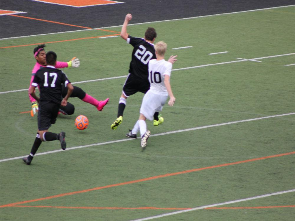 Senior Ryan Bogan kicks the ball past two thunderbolt defenders.