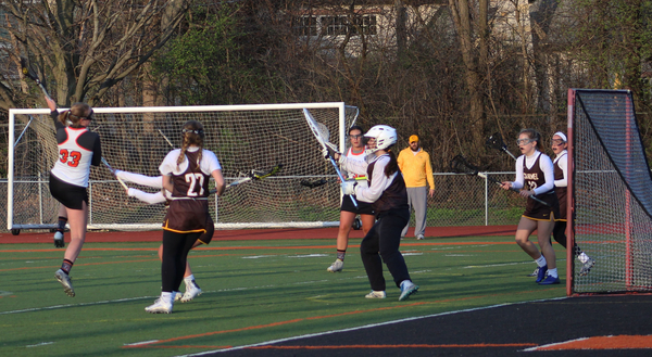 Senior+Sarah+Pavelske+jumps+in+the+air+to+to+shoot+as+she+rolls+the+crease+prior+to+scoring.