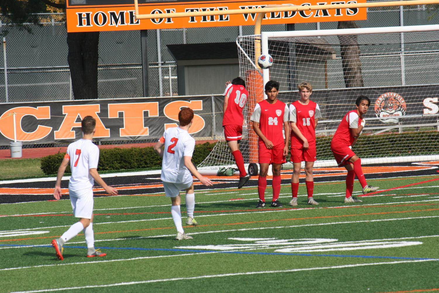 Ryan Wittenbrink (#2) kicks his first goal of the game over the head of three Mundelein defenders. Photo courtesy of Maddy Wittenbrink