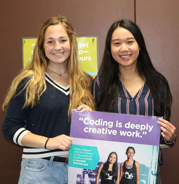 Graton (left) and Tong (right)  holding one of the many posters hung around the computer science classroom.