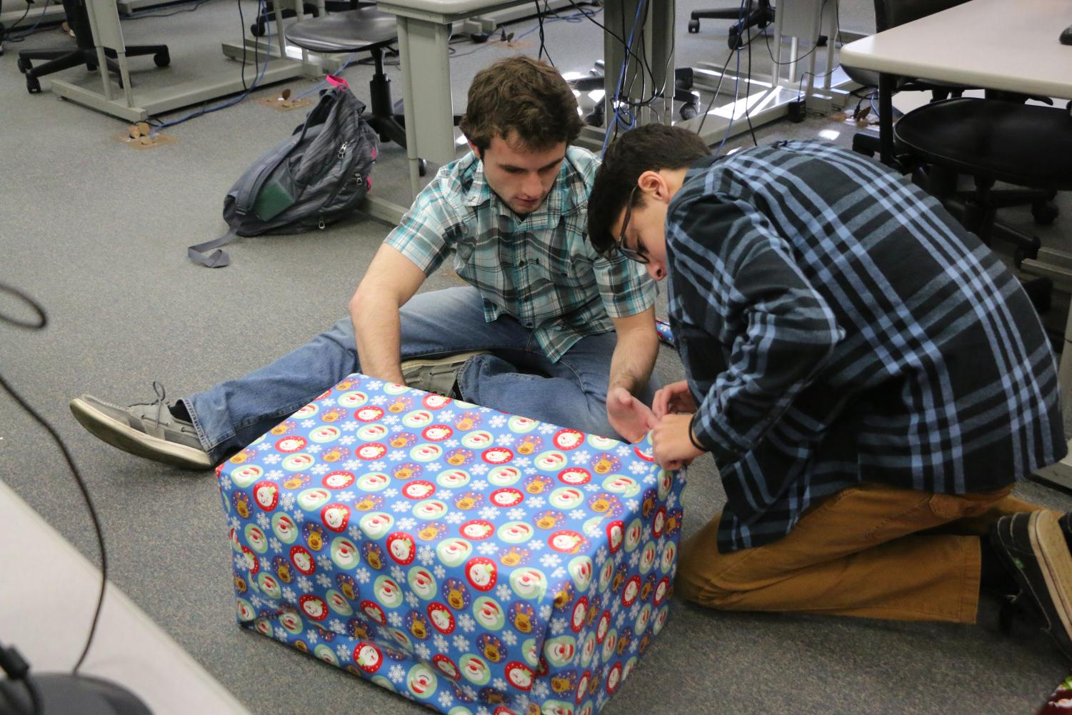 Students of Dr. Kellum's WISH class, Daniel Ritz and Gregory Yonan, wrap a present they bought for their WISH family.