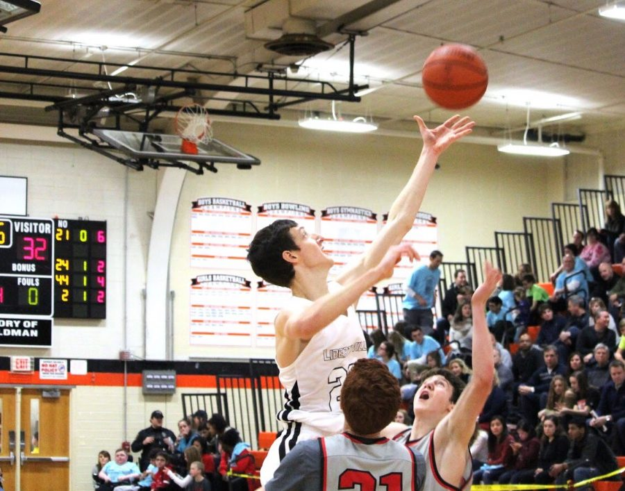 Battling+for+an+offensive+rebound%2C+6%E2%80%998%E2%80%99%E2%80%99+senior+forward+Drew+Peterson+towers+over+two+Mundelein+players+as+he+reaches+for+the+ball.