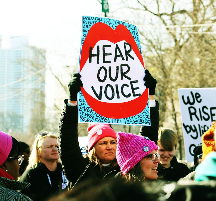 A+woman+holds+up+a+sign+reading+%E2%80%9CHear+our+voice%E2%80%9D+as+she+participates+in+the+Women%E2%80%99s+March+on+Chicago%2C+which+began+at+Columbus+Drive+near+Buckingham+Fountain+and+stretched+all+the+way+to+Randolph+Street%2C+according+to+WTTW.
