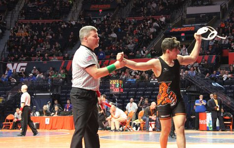 Pucino's victory in the Class 3A 132-pound weight group third-place match is announced by the referee, as he raises Pucino's arm. Pucino waves to his teammates who supported him during the tournament, with his head gear in hand.