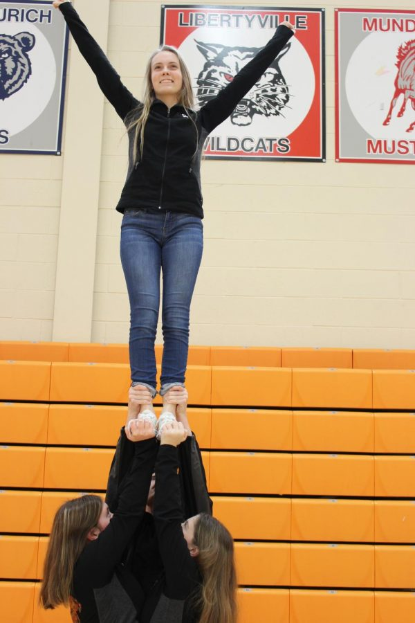 Freshman Maggie Vickers being lifted in a cheer stunt by her teammates, junior Jackson Bogus, sophomore Isabella Zalewski and freshman Olivia Guarino.