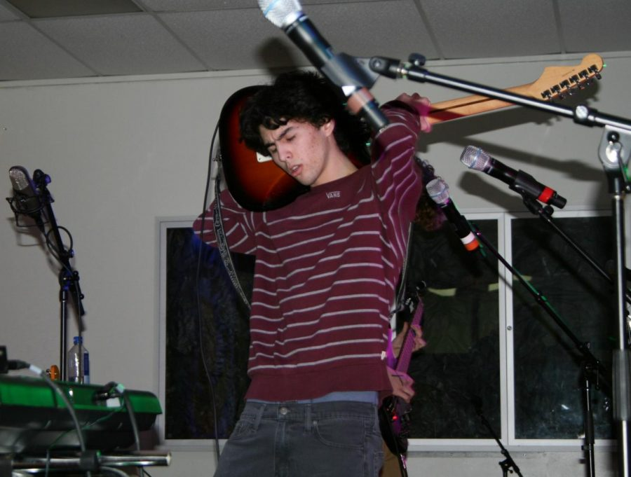Junior Isaac Rodriguez, lead singer and guitar player for Fun Monkey, continues to play guitar as he holds it behind his head.