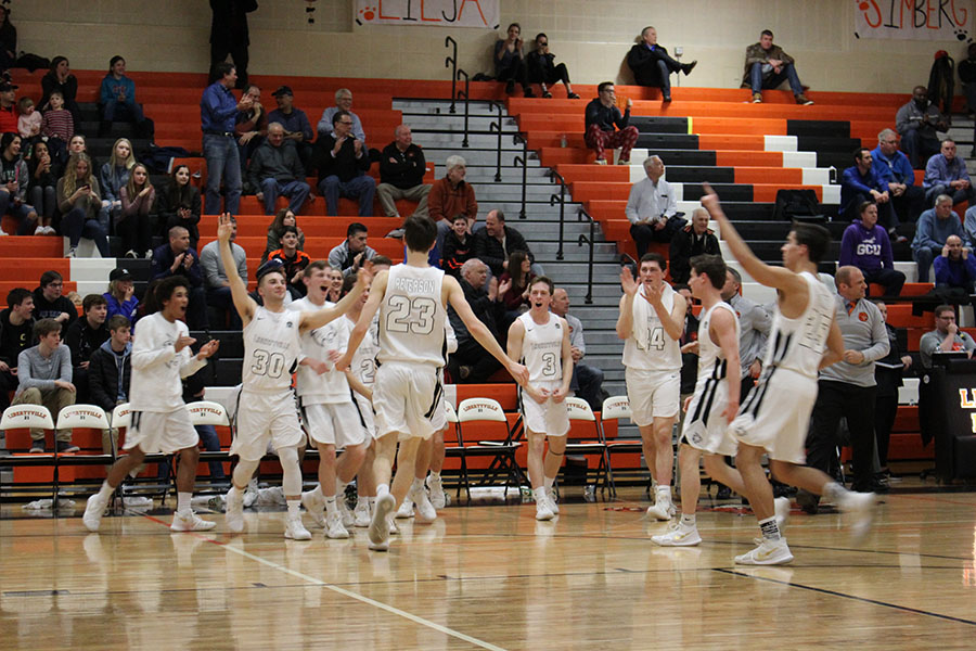 Drew Peterson celebrates with his teammates, who are ecstatic after a huge 3-point shot, during their home game against conference opponent Lake Zurich.