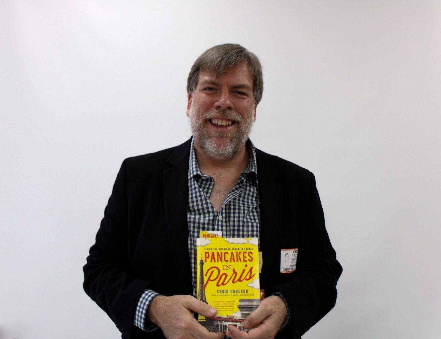 Craig Carlson poses with his book, Pancakes in Paris, which details the story of how Mr. Carlson came to open his own restaurant in Paris.