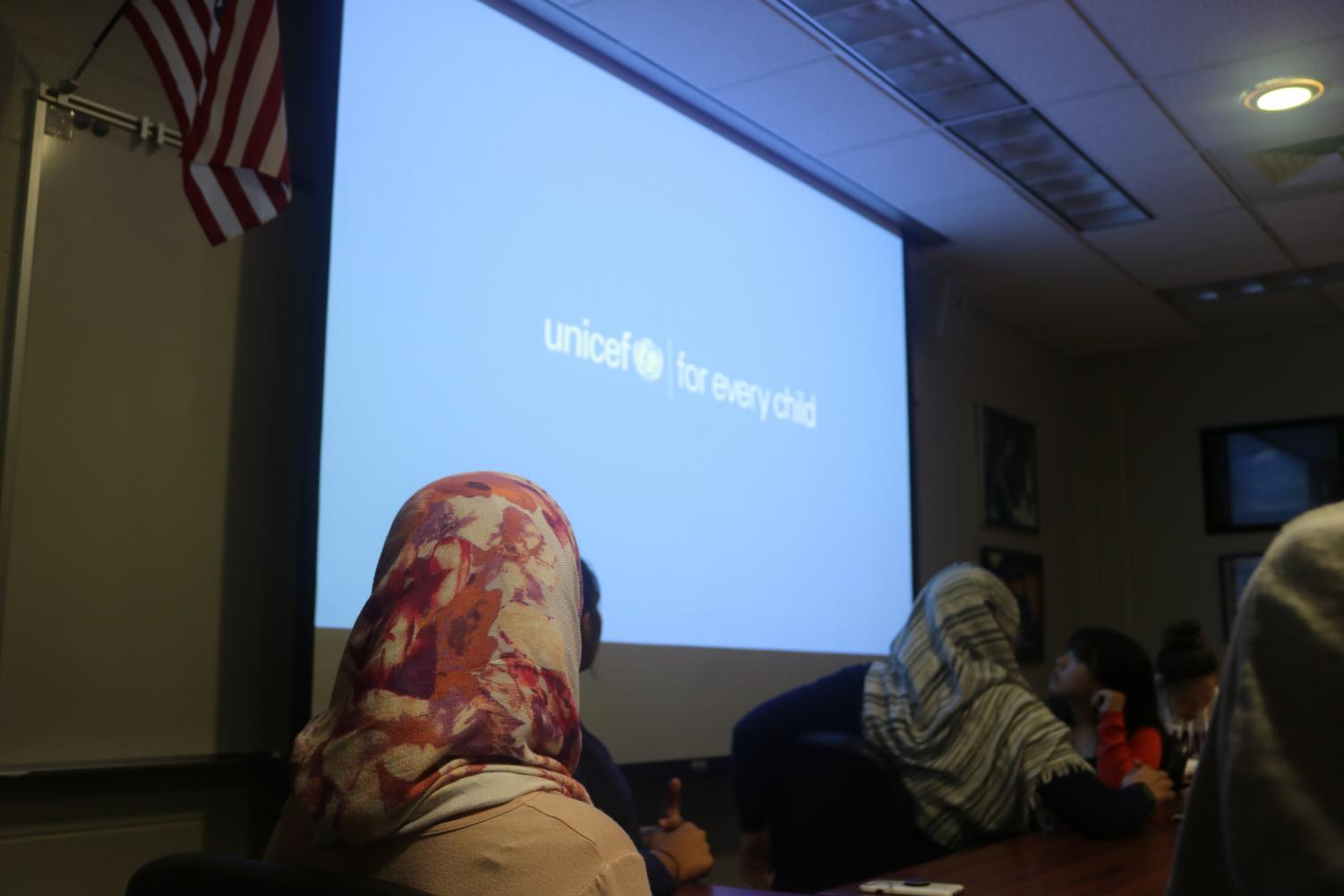 Students interested in UNICEF watch an informational video about how the organization helps children around the world.
