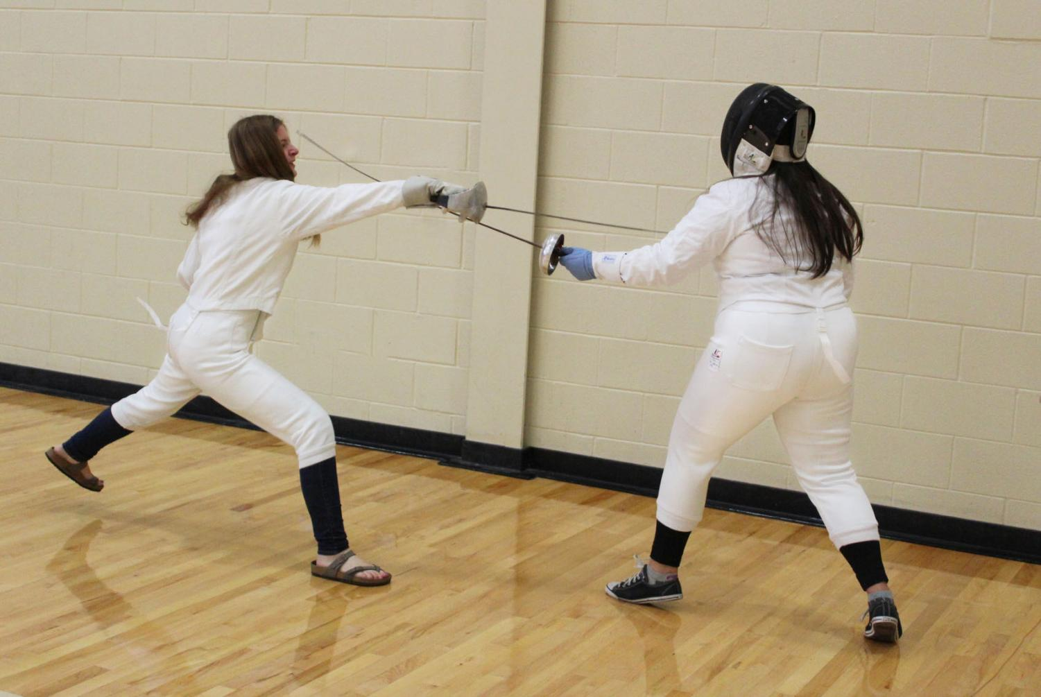 Although fencing is generally recognized as a sport, LHS offers it as a club. Seniors Anna Schellin and Charlotte Stevenson practice for a match.