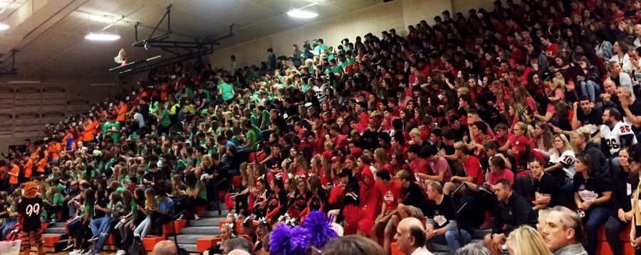The freshman, in green, and the sophomores, in red, wait for the assembly to start. The band -- far left, in orange -- performs while students arrive.