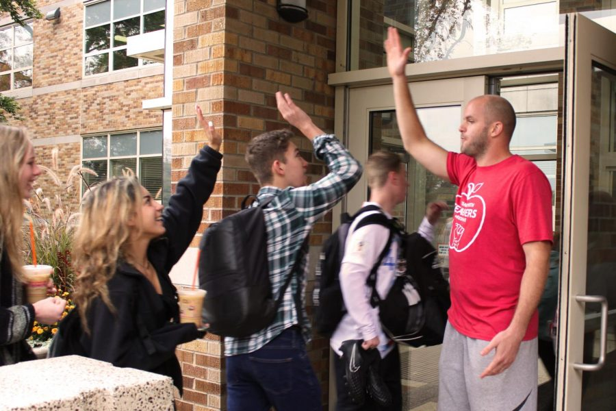 To boost students' spirits, Mr. Adam Stuart high fives students as they walk into the school on the last day of Red Ribbon Week.