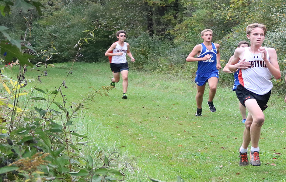 LHS sophomore Liam Tucker (right) and senior Jonathan Timm (left) run alongside their Lake Zurich opponents as they pass the one-mile mark.