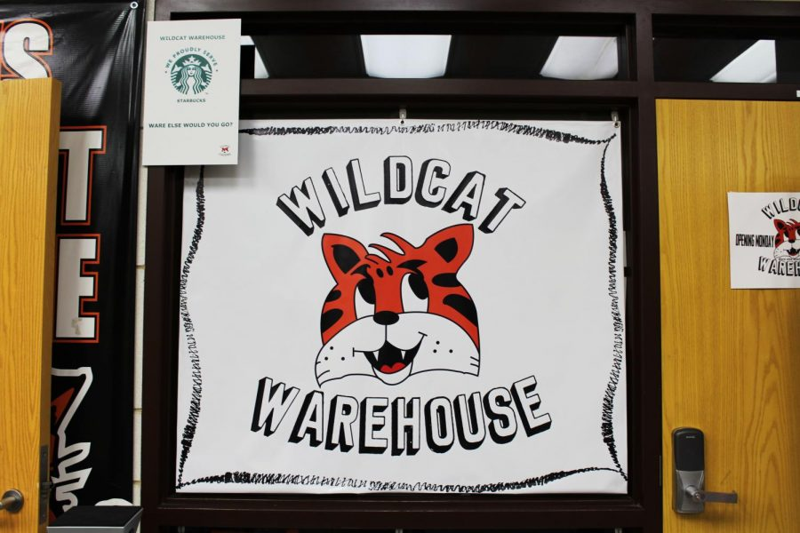 The Wildcat Warehouse is open before school every morning in the main lobby. Their logo, featured on this sign hanging next to the Spirit Store, was designed by senior Brandon Fisher.