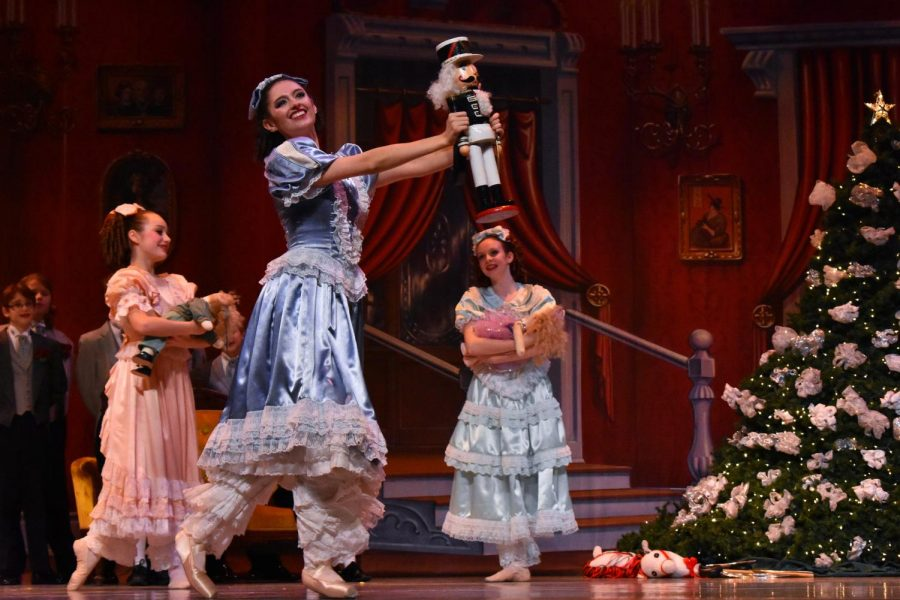 Clara shows off her nutcracker while the other children, danced by the Dance Center North ensemble, admire from afar.