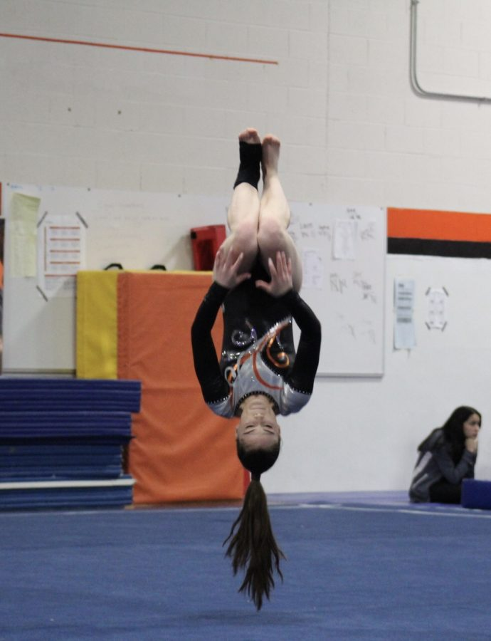 During+the+middle+of+her+floor+routine%2C+Amy+Magill+completes+a+back+handspring-back+handspring-tuck+combination%2C+helping+her+to+achieve+a+final+score+of+7.15.