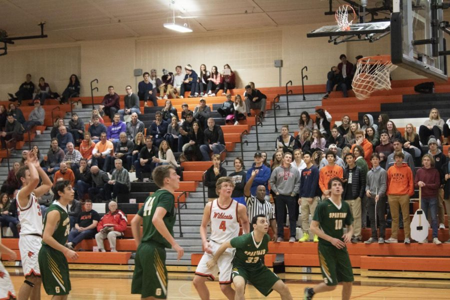 Senior Travis Clark makes his second free-throw attempt as players from both sides look on.