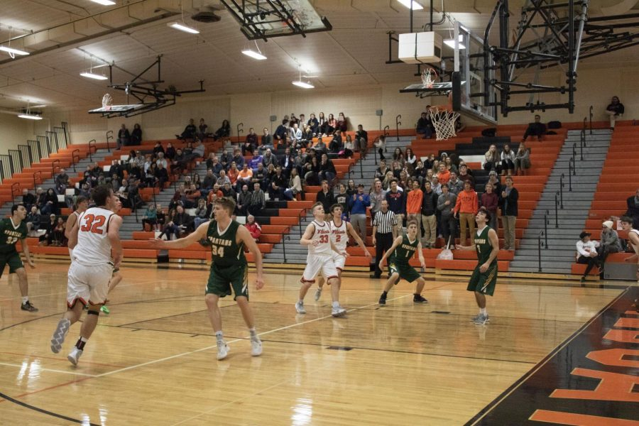 Brimming with anticipation, the players watch as a another basket is scored for LHS by Travis Clark.