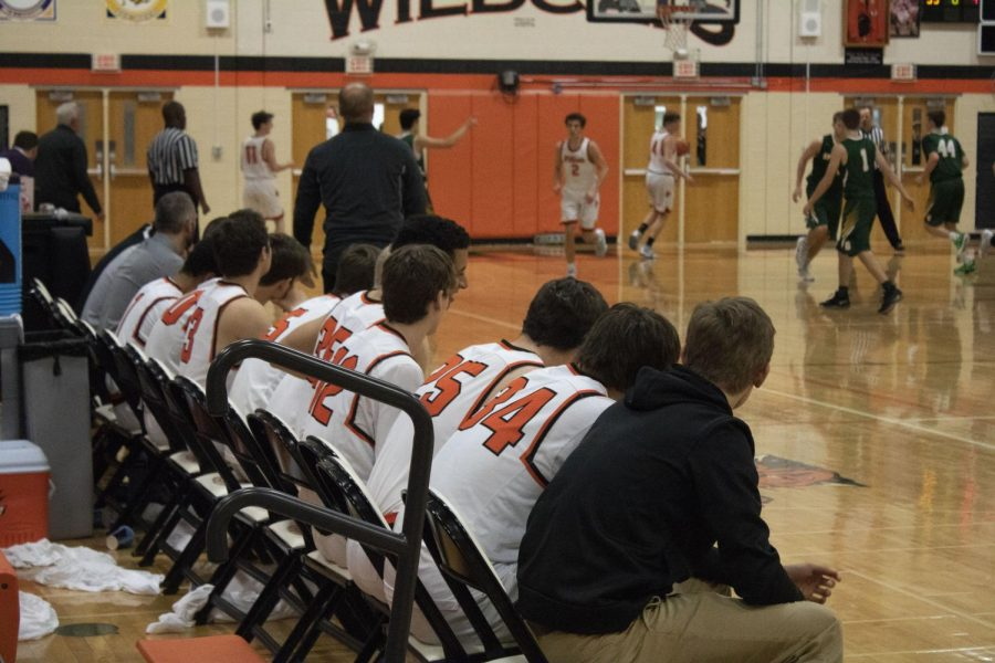 Coaches and players on the bench watch their teammates intently.