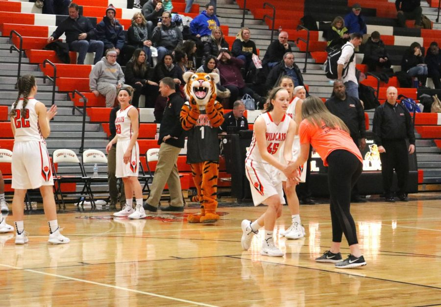 Members of LHS girls varsity basketball preform a handshake with DOI staff member, and senior Maggie Evers before the game.