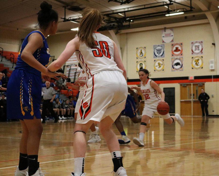 #50, junior Lydia Crow guards as her teammate, fellow junior Margaret Buchert #32 makes her way down the court.