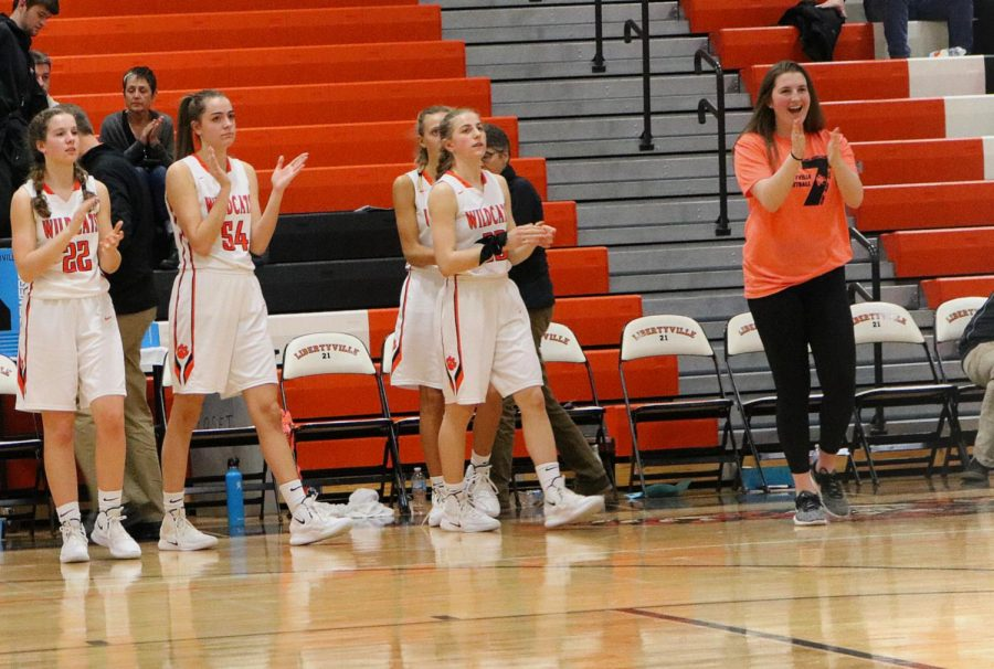 The team celebrates a victory over Warren with the final score ending 56-41.