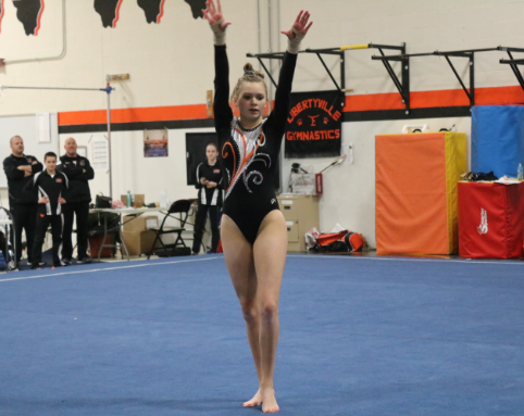 Grace Neuberger poses right after beginning her floor routine and going into a turn.