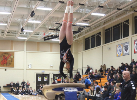 Swanson does a brief handstand on the vault before twisting and landing her jump.