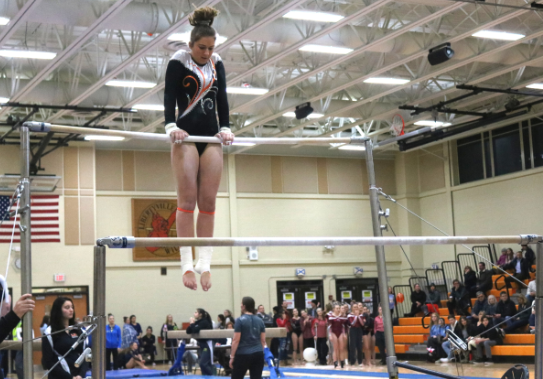 Swanson prepares to do a flip on the uneven bars.