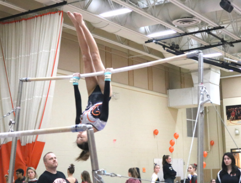 Bertsch competes on the uneven bars. After jumping onto the higher one, she does multiple flips.
