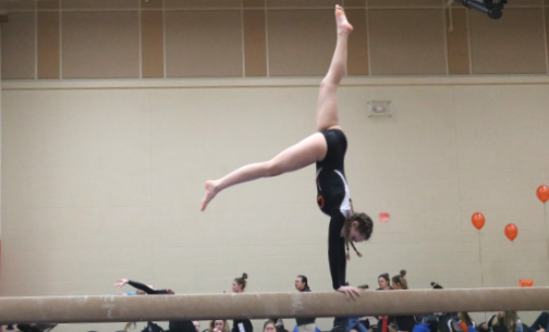 Emaline Frey maintains her balance while performing a front walkover on the beam.