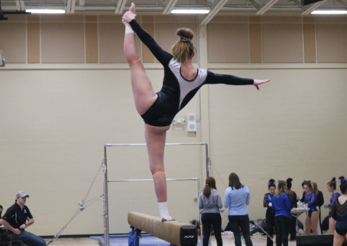 Swanson performs a leg hold straight up on the beam for about two seconds.