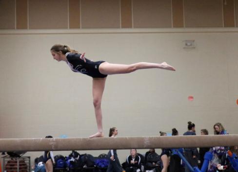 Sophomore Lauren Mills balances herself on one leg on the beam.