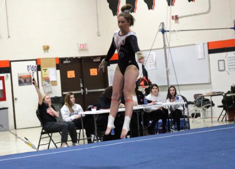 Junior Maddie Swanson prepares to land as she goes through her floor routine.