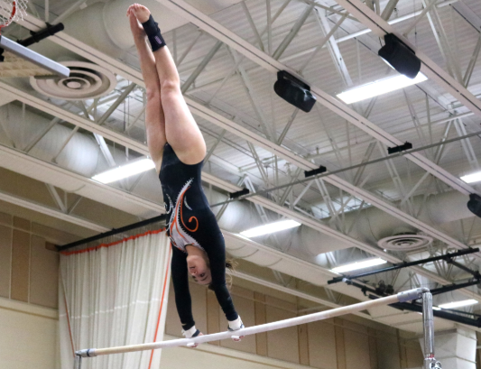 Junior Cameron Hamilton competes on the uneven bars and jumps up to the higher one, where she holds a brief handstand.