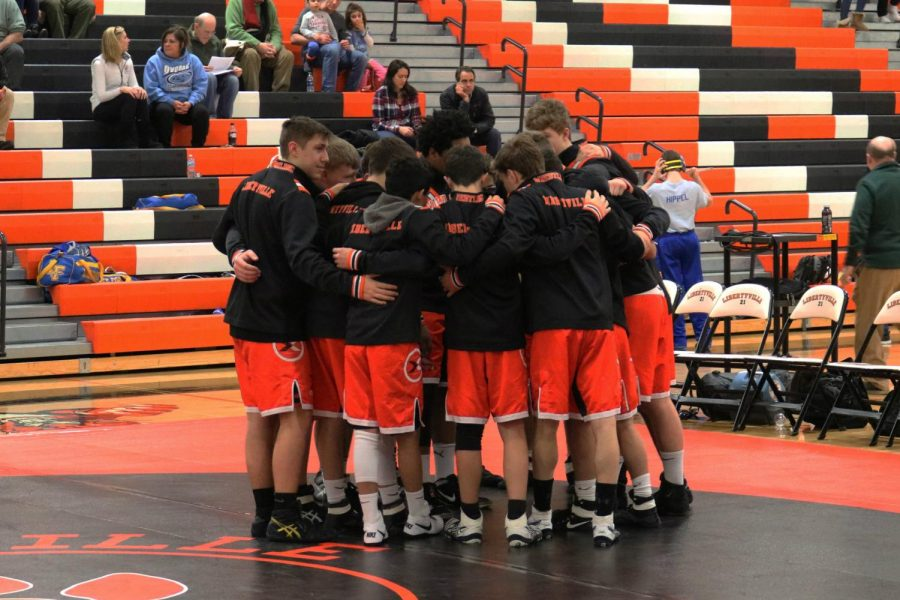 The Libertyville varsity team huddles before the matches begin.