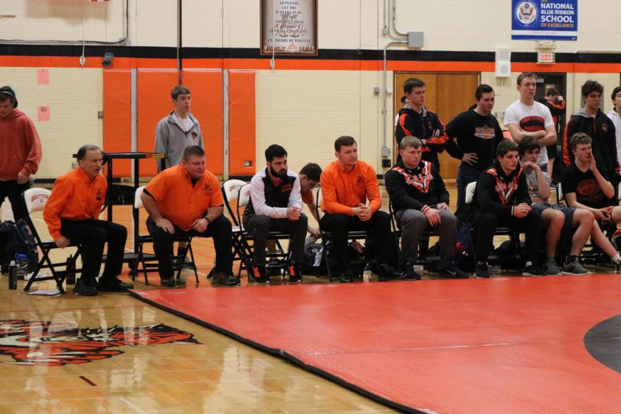 While wrestling, each competitor receives support and shouts of advice from the rest of the team -- coaches and athletes -- on the sidelines.