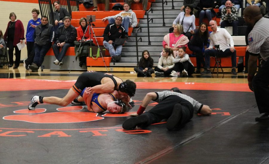 One of the referees gets close to the ground in order to verify if one of the Libertyville wrestlers gets a successful pin on the opponent.