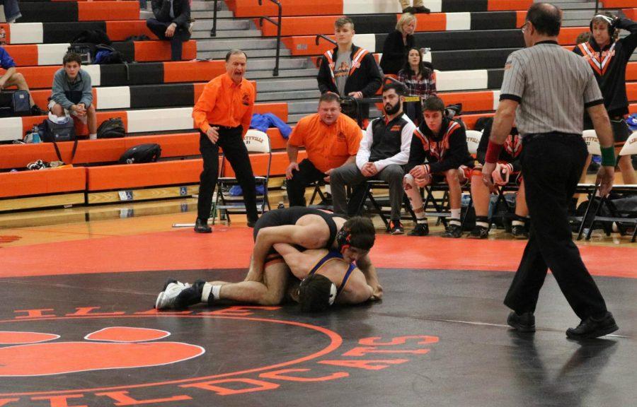 Senior Bennett Whitney brings his opponent down to the mat.