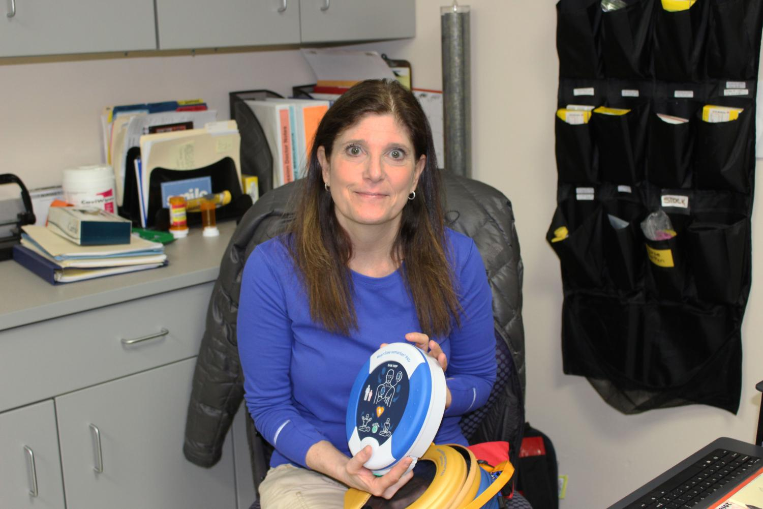 Ms. Alisa Wasserman, one of the school's nurses, holds an Automated External Defibrillator, which is used to help revive victims of cardiac arrest.