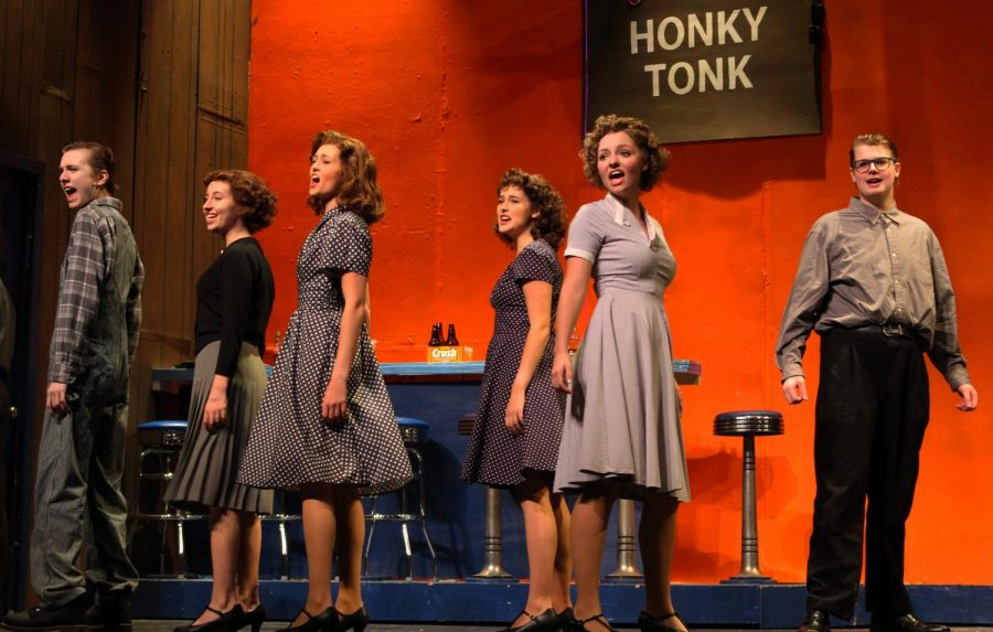Senior Amanda Gourley as Henrietta and members of the ensemble sing