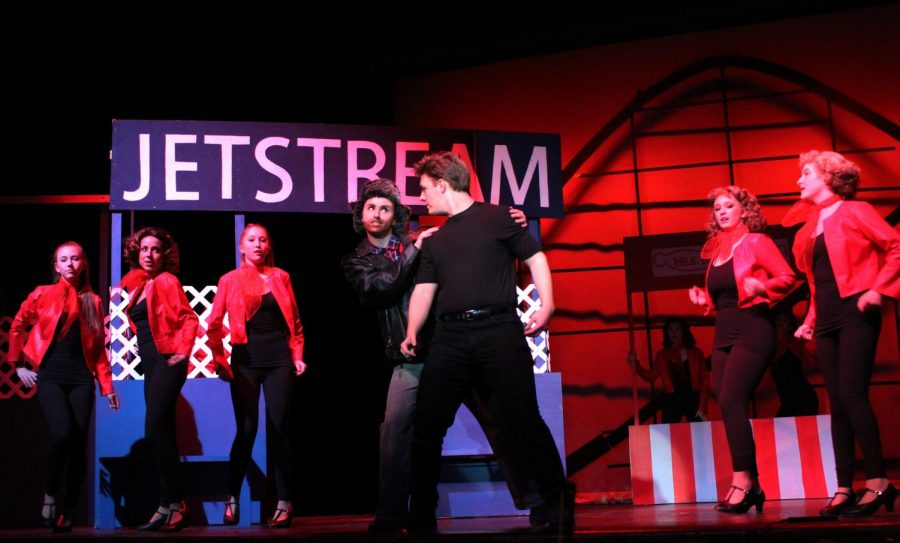 The musical is set in a small Midwest town in the summer of 1955, shown through the leather jackets and neck scarves worn by the ensemble. Erdmann and Sterner perform