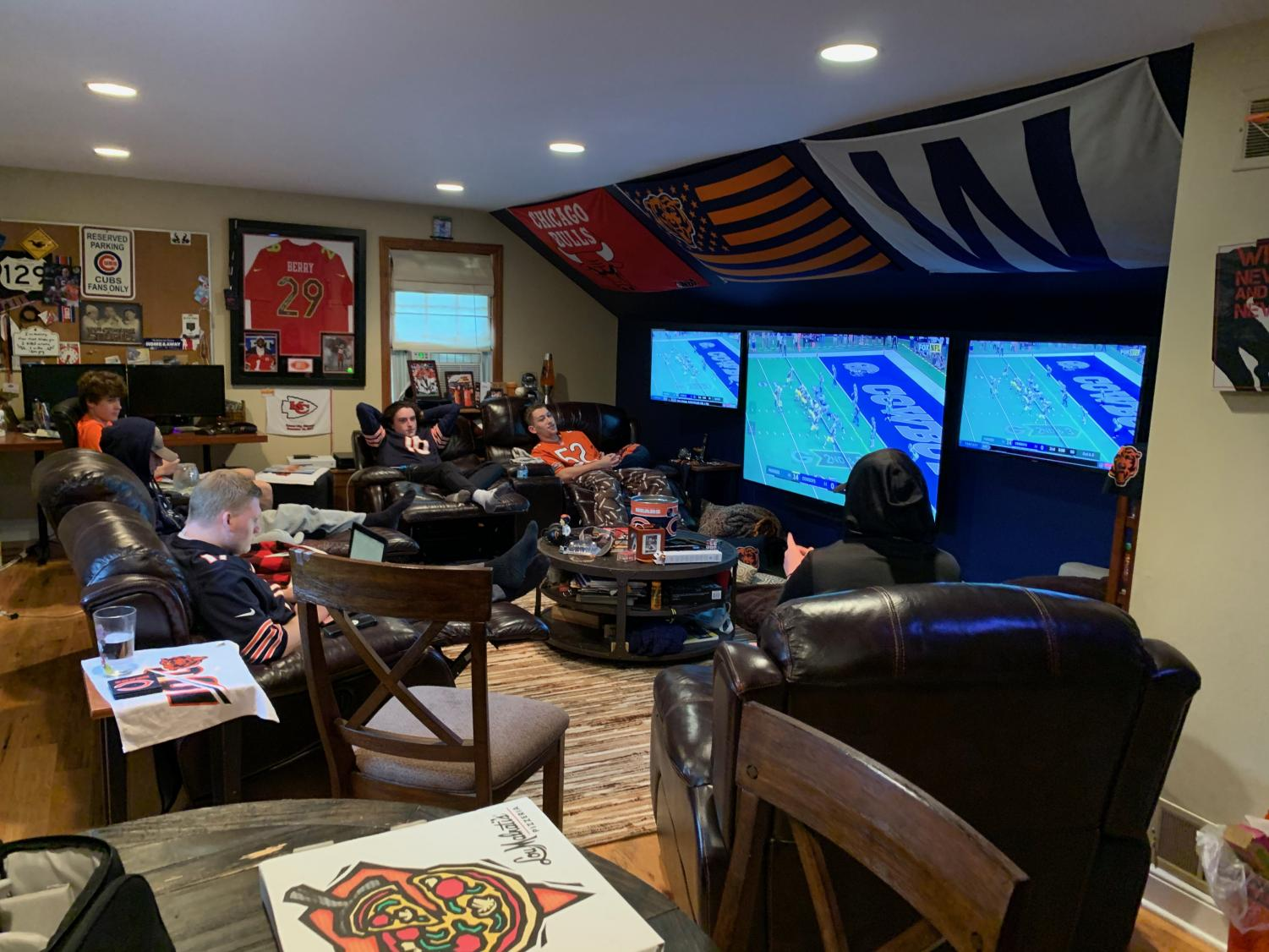 Senior Jarod Rosenbloom's fantasy football league gathers around to watch the games and track their players. The focal point of their room consists of three TVs: one in the center to play their main game and the other surrounding two to watch NFL Red Zone.
